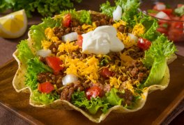 beef taco salad topped with chedder and sour cream