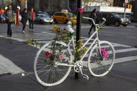 A memorial ghost bike stands at the corner of Pitt Street and Houston Street in the Lower East Side of Manhattan. Bikes painted white are left on the street by friends and relatives when a cyclist has died in an accident. They serve both as a memorial tribute to the victim and a reminder to cyclists and drivers of how dangerous the busy streets of New York City can be. This bike is decorated with plastic flowers. Cars and taxis can be seen driving east along Houston Street. In November 2014 a 61 year old cyclist was hit and killed by a livery cab traveling along Houston Street.