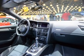 Interior on a Audi A5 Sportback luxury sedan with leather and fabric seats, manual six speed gear shift and a large information display on the dashboard.