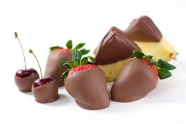 A variety of fresh fruits all clad in creamy delicious chocolate.  PIneapple, strawberries and cherries.  Shallow dof.