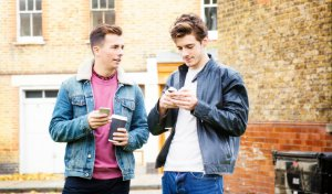 Two young british men social networking on mobile phones outdoors in the streets of London. One is looking at the other.