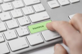 Online insurance concept. Man press keyboard button with text insurance.