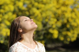 Woman breathing deep in spring or summer with a yellow background