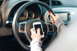 Helpless driver dialing car insurance company for road assistance. Female driver in the driving seat holding steering wheel and dialing or texting on smartphone. Image taken with Nikon D800 and 24- 70 lens, developed from RAW.